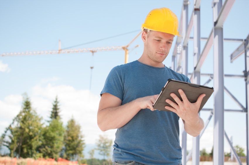Construction worker reviewing plans on digital tablet